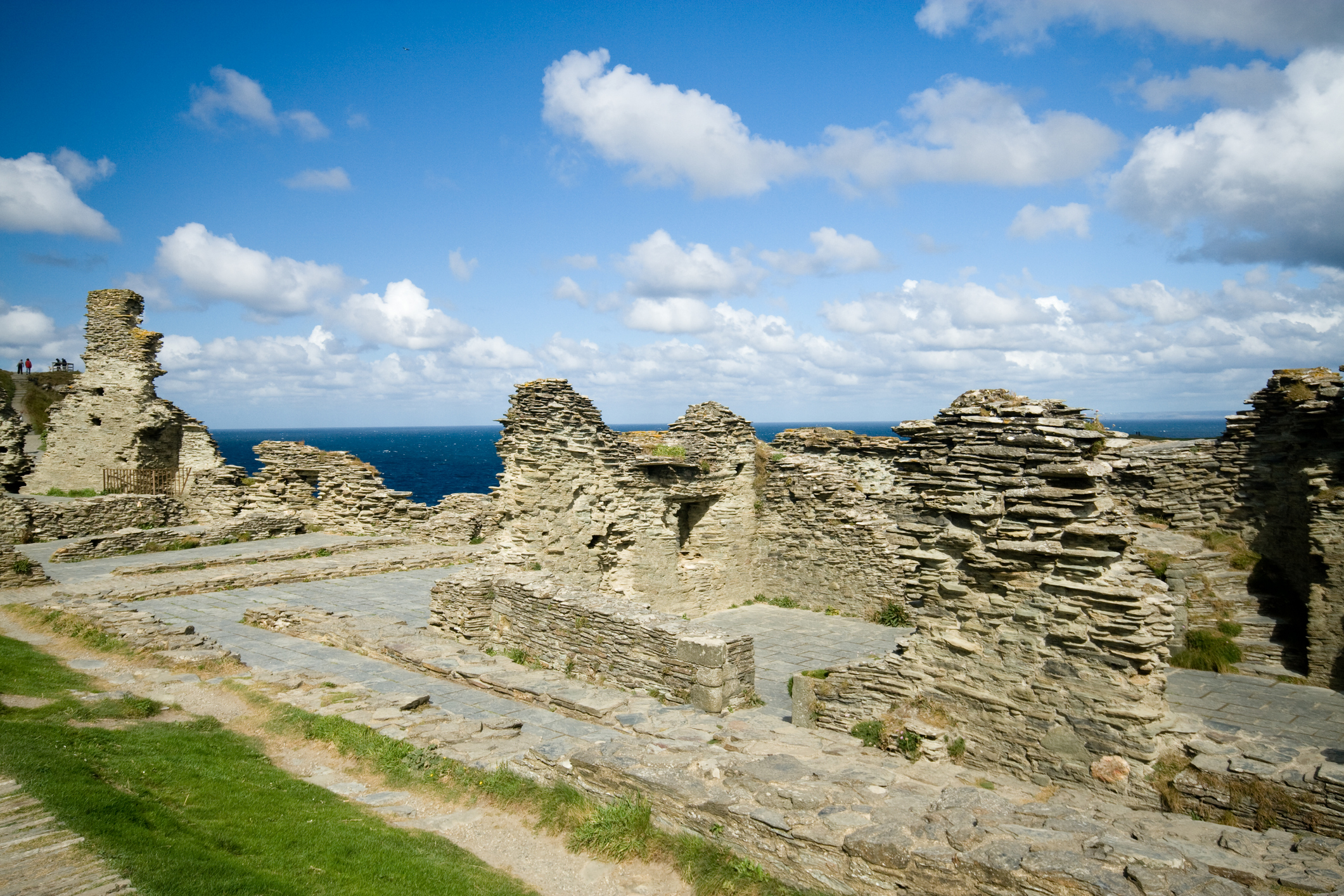 A landscape view of Tintagel Castle ruins, in north Cornwall, England, with the remains of walls and floors in stone