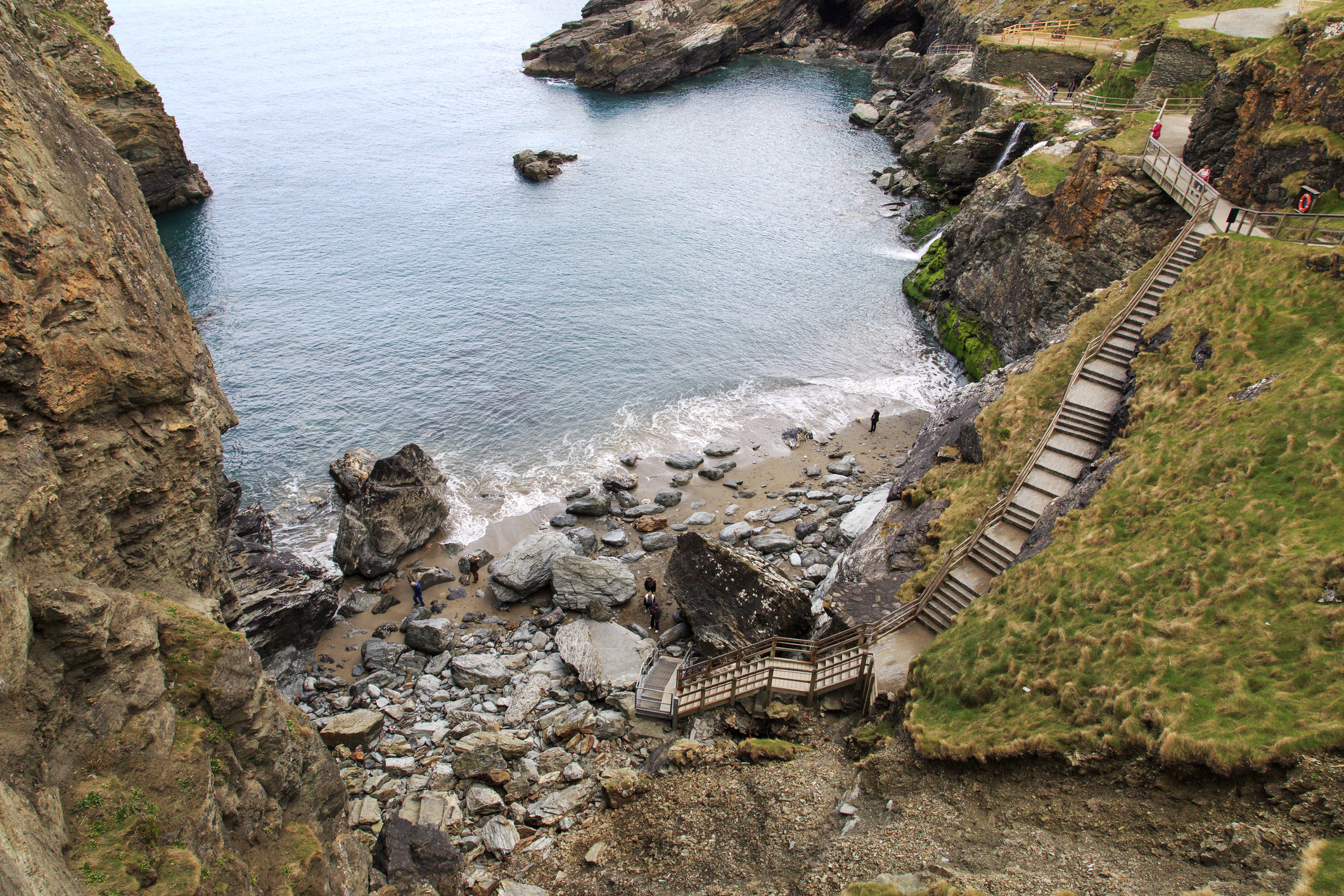 Cornwall, UK: April 14, 2016: Tourists enjoying the beach at the bottom of some steps at Tintagel. Tintagel is maintained by English Heritage who are also responsible for Stonehenge and many other ancient sites across England.
