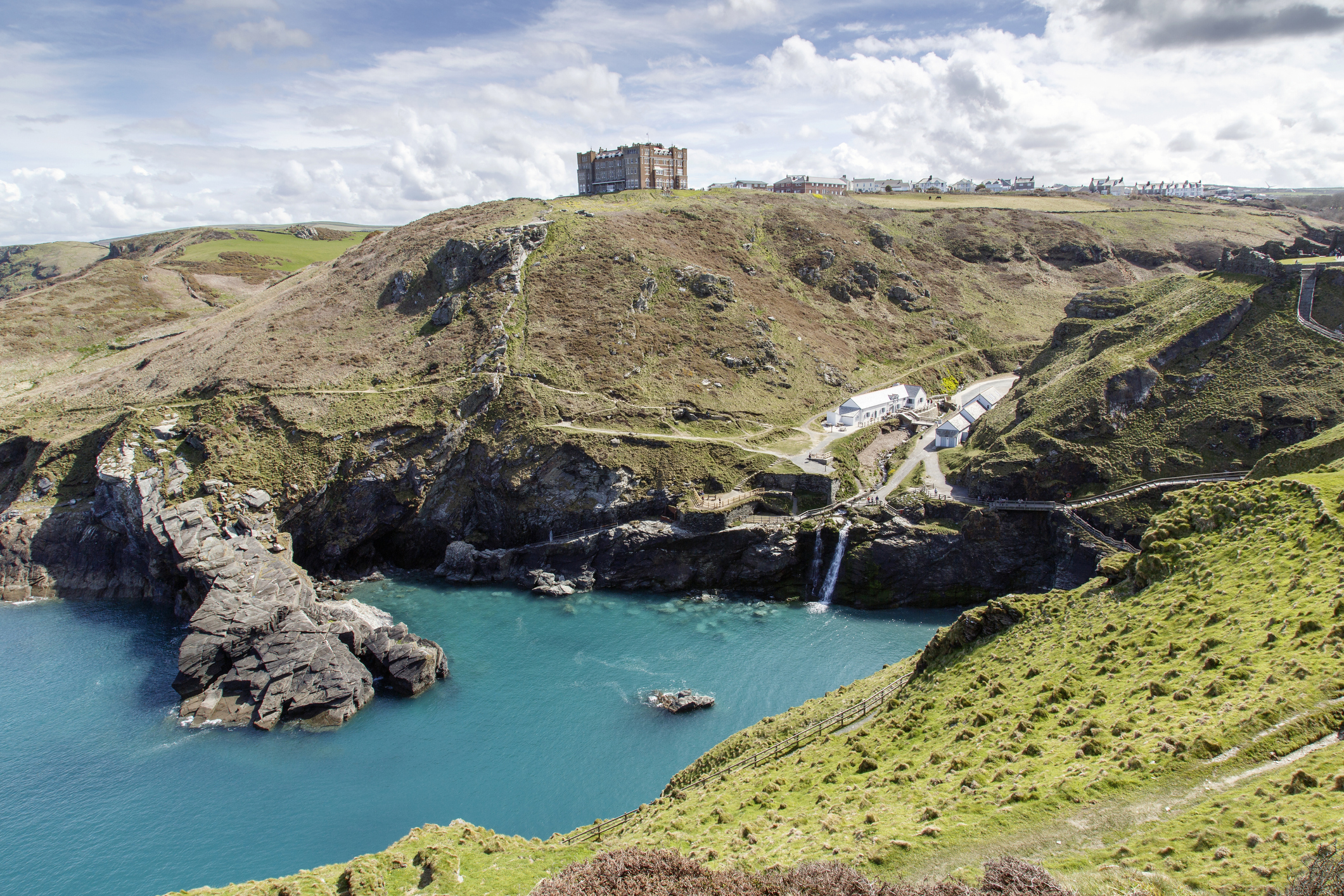 Tintagel, Cornwall, UK: April 14, 2016: A view of the main entrance to Tintagel Castle in the valley and Hotel Camelot on the cliff. There is a  beach cafe, visitors centre, public facilities and the booking desk and the entrance. The castle is maintained by English Heritage who are also responsible for Stonehenge and many other ancient sites across England.