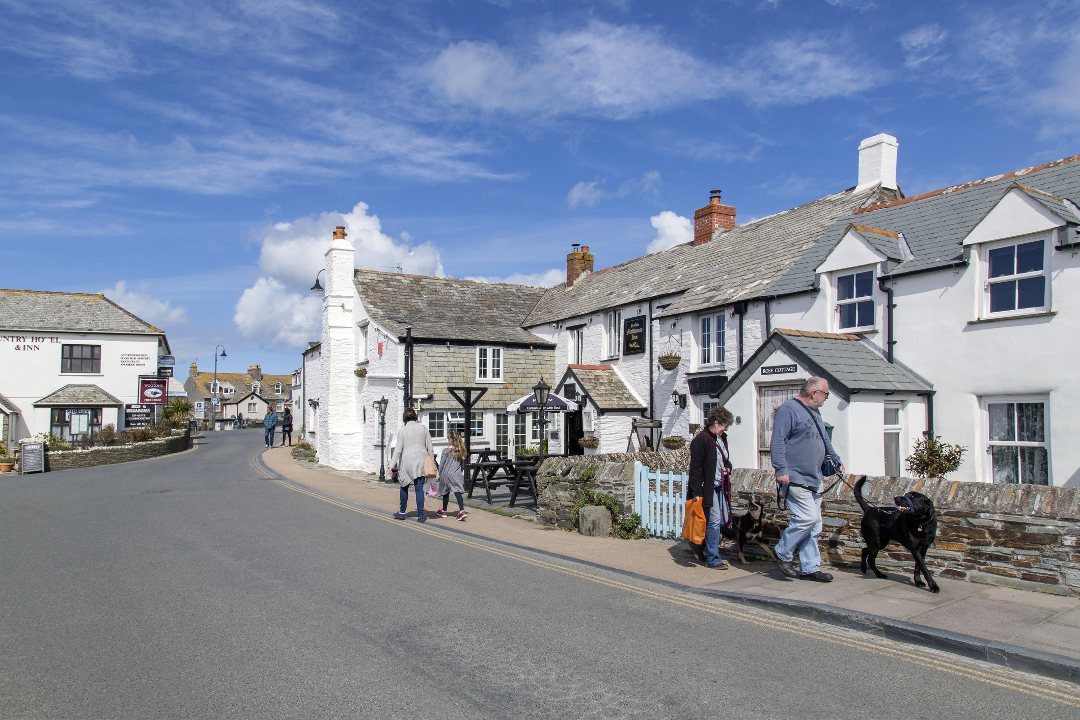 Tintagel, Cornwall, UK: April 14, 2016: Street view of the popular tourist village of Tintagel in Cornwall. A couple are walking their dogs and a mother and daughter are walking away from the camera. A pub is to the right and a Hotel is in the background.