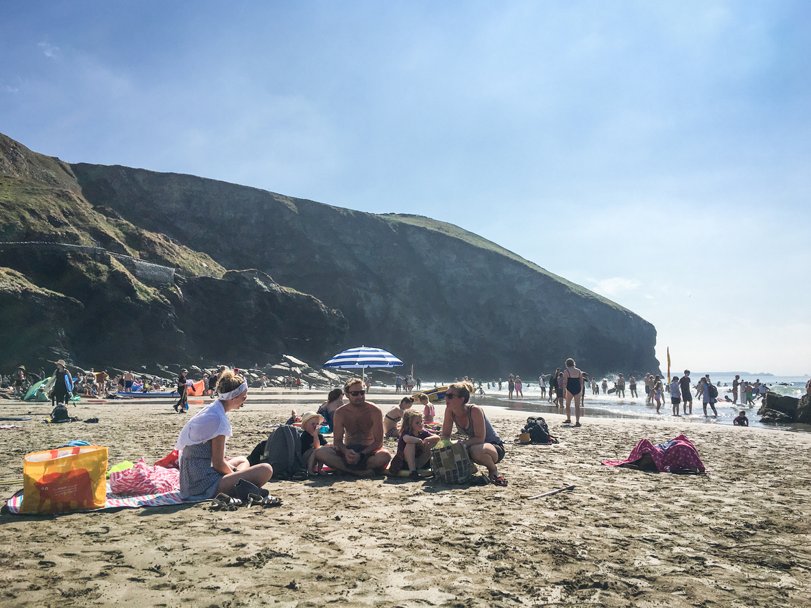 Trebarwith Strand Beach, Cornwall, England - August 5th, 2018: People hanging out at the rocky beach, a dog friendly beach at Trebarwith in North Cornwall during summertime.