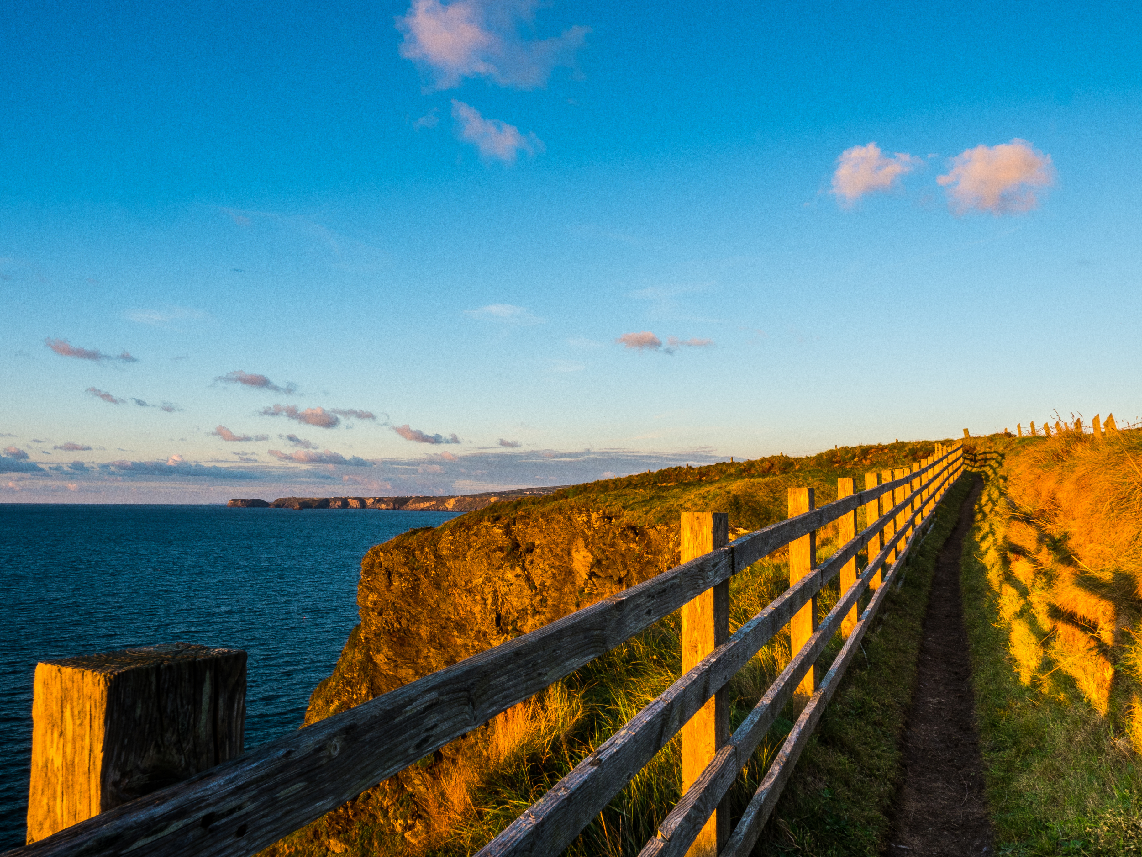 Coastal path leading the way along cliff tops in Cornwall at sunrise