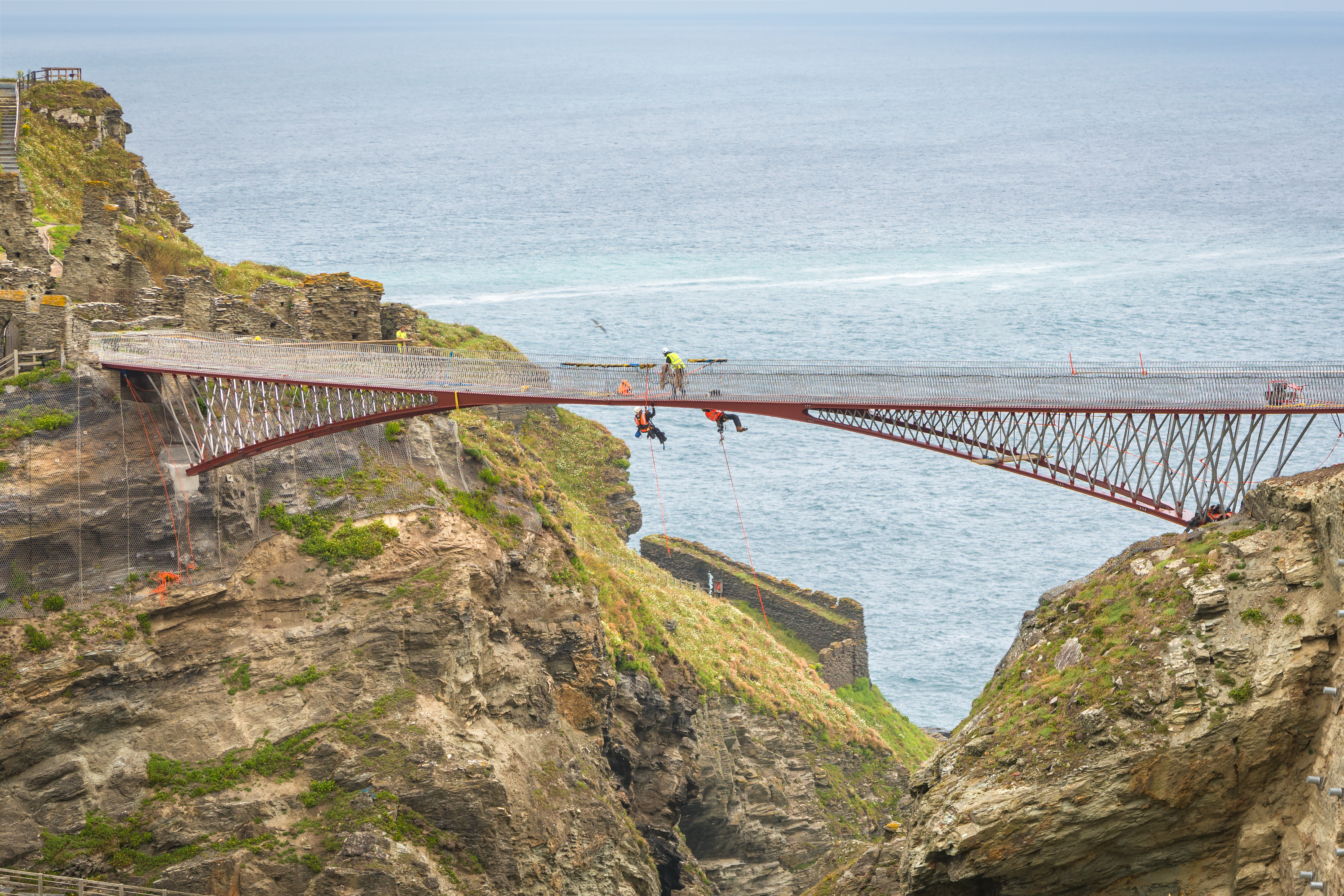 Tintagel, United Kingdom - July 24, 2019: Unidetified workers build on heights new Tintagel bridge. Copy space on sea surface.